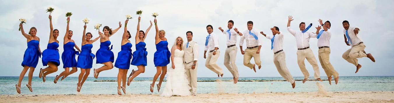 A huge wedding party jumps for joy on the beach