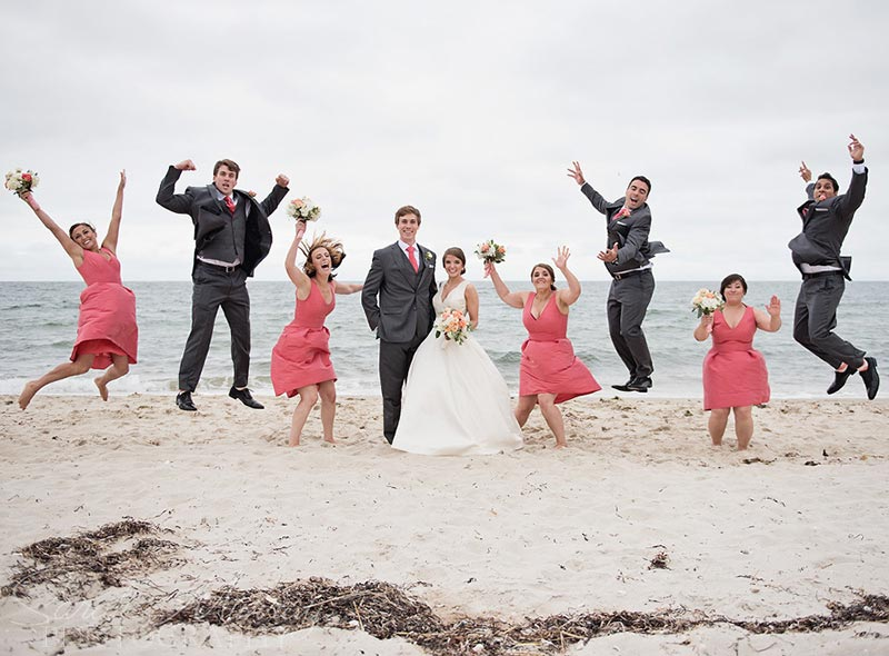 A wedding party jumps for the camera